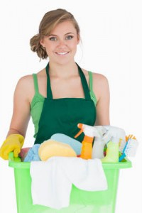 Portrait of young maid carrying cleaning supplies over white background